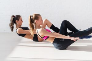 Two sporty women doing exercise abdominal crunches, pumping a press on floor in gym concept training exercising workout fitness aerobic side view. ** Note: Shallow depth of field